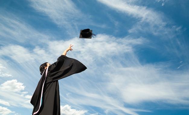 Uma pós-graduação jogou um chapéu para o céu da cerimônia de formatura no dia da formatura