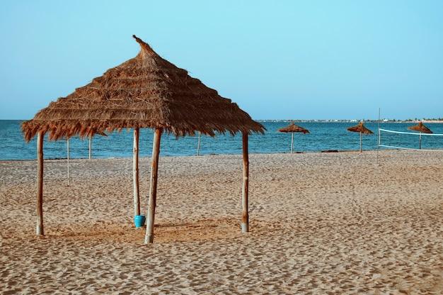 Uma praia à beira-mar com guarda-sóis de palha na areia na tunísia.