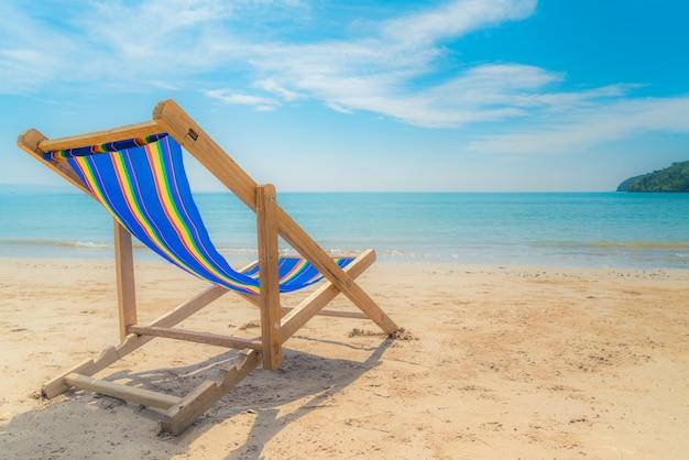 Uma praia cadeiras na areia branca com céu azul e mar de verão