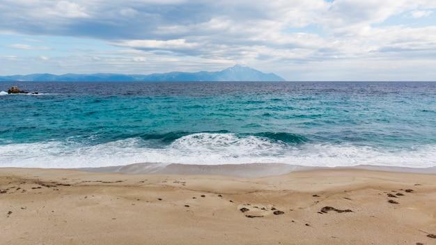 Uma praia com ondas azuis do mar egeu e montanha