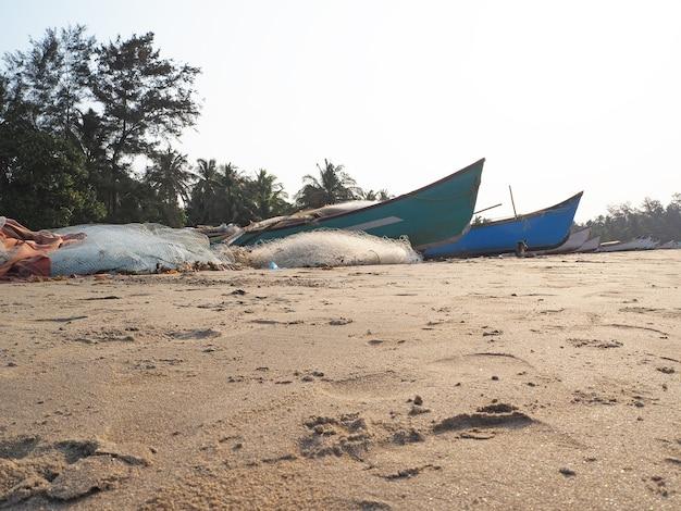 Uma praia de areia com barcos de pesca e redes ao lado deles ao pôr do sol. o conceito de pesca