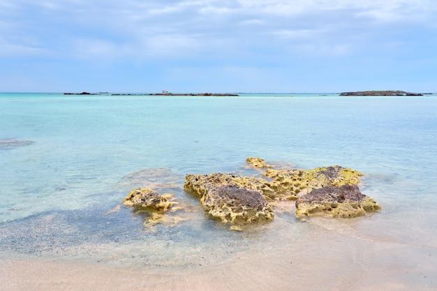 Uma praia de areia elafonissi na ilha de creta com águas azul-turquesa.