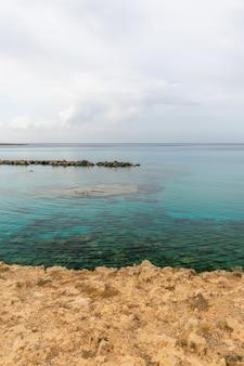 Uma praia pitoresca com água cristalina está localizada nas margens do mar mediterrâneo.