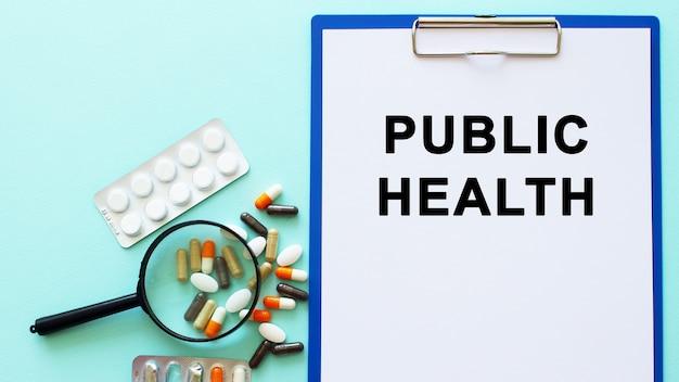 Uma prancheta com papel encontra-se sobre uma mesa perto de drogas e uma seringa. inscrição saúde pública. conceito médico.