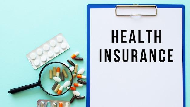 Uma prancheta com papel encontra-se sobre uma mesa perto de drogas e uma seringa. inscrição seguro de saúde
