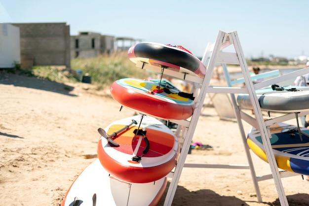 Uma prateleira de pranchas de surf sup no conceito de férias da costa do mar
