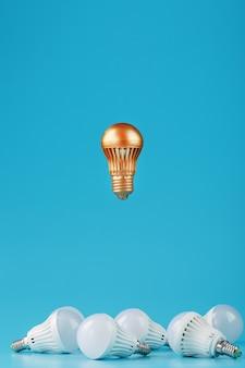 Uma proeminente lâmpada dourada levita acima de um ambiente de lâmpadas brancas.