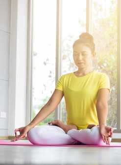 Uma professora de ioga asiática vestindo uma camisa amarela está treinando seu corpo para ser forte e saudável com o yoga.