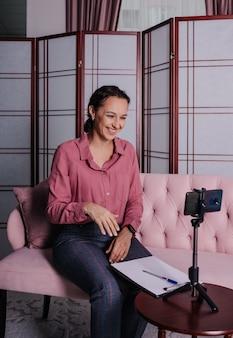 Uma psicóloga branca com uma camisa rosa senta no sofá e faz uma consulta online por telefone