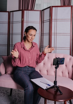 Uma psicóloga com uma camisa rosa está sentada no sofá e conduzindo uma consulta online usando seu telefone