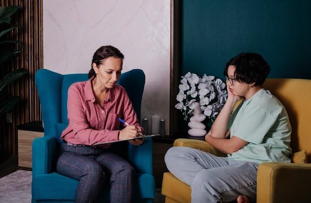 Uma psicóloga conduz uma consulta para uma adolescente no escritório. problemas de adolescentes