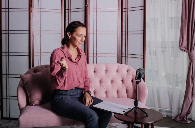 Uma psicóloga de blusa rosa está sentada no sofá e conduzindo uma consulta online
