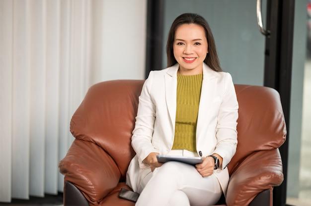 Uma psicóloga se senta no sofá enquanto espera para consultar um paciente.