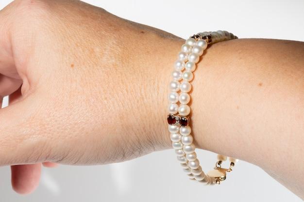 Uma pulseira de pérolas em uma mão isolada em um fundo branco.