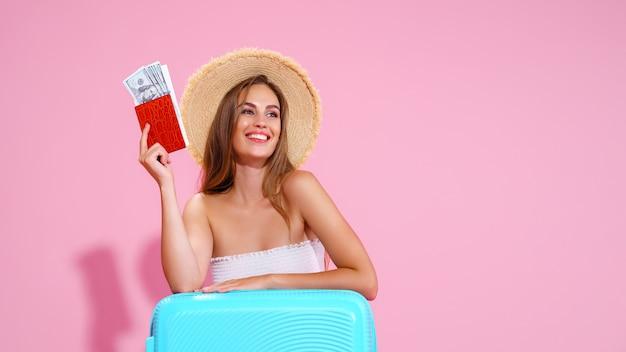 Uma rapariga com um chapéu de palha tem nas mãos os bilhetes para uma viagem uma mala