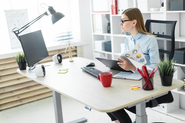 Uma rapariga de óculos se senta em uma mesa no escritório