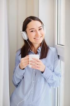 Uma rapariga nos auscultadores com uma caneca de bebida quente nas mãos pela janela.