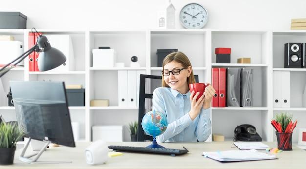 Uma rapariga nos vidros está sentando-se em uma tabela, prendendo um copo vermelho em suas mãos e olhando o globo.