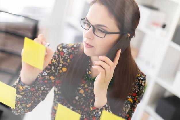 Uma rapariga que está no escritório perto de uma placa transparente com etiquetas e que fala no telefone.