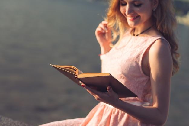 Uma rapariga que lê um livro na margem do rio.