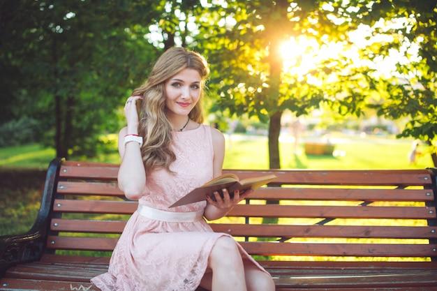 Uma rapariga que lê um livro que senta-se em um banco no por do sol.