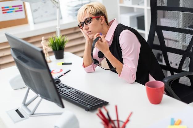 Uma rapariga que senta-se em uma tabela do computador e que prende sua mão no mordente.