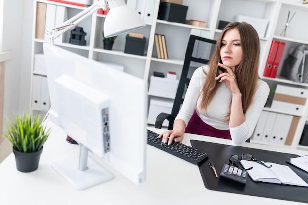 Uma rapariga que senta-se em uma tabela e que datilografa no teclado.