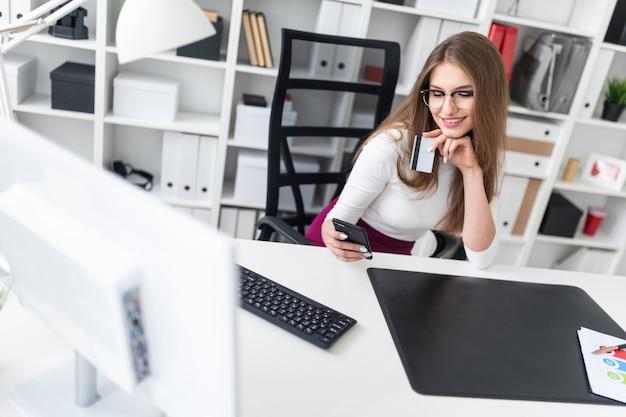 Uma rapariga que senta-se em uma tabela e que prende um telefone e um cartão de crédito.