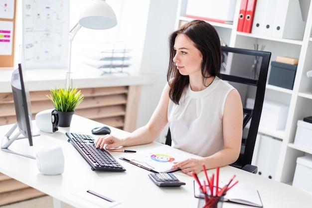 Uma rapariga que senta-se no escritório em uma mesa do computador e que trabalha com originais.