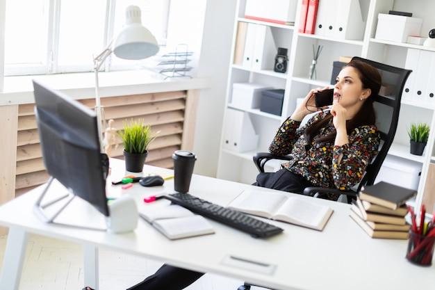 Uma rapariga que senta-se no escritório na mesa do computador e que fala no telefone.