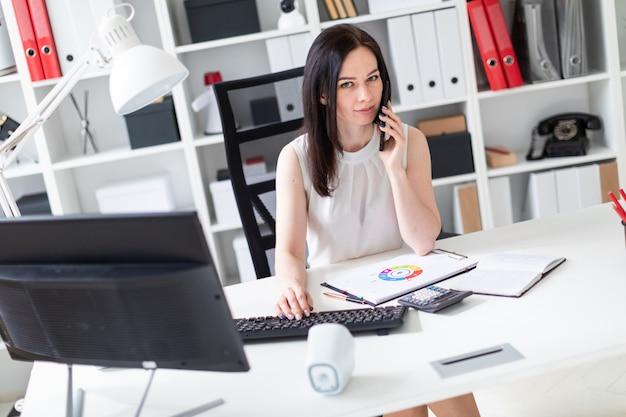 Uma rapariga que senta-se no escritório na mesa do computador, falando no telefone e trabalhando com originais.
