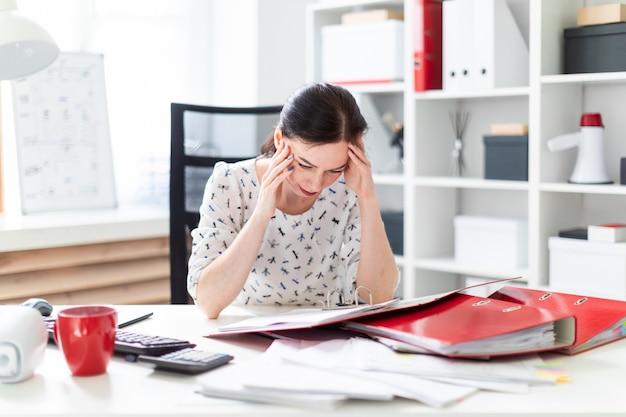 Uma rapariga que senta-se no escritório na mesa do computador, trabalhando com originais e prendendo as mãos em sua cabeça.