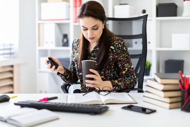 Uma rapariga que senta-se no escritório na tabela do computador e que prende um vidro do café.