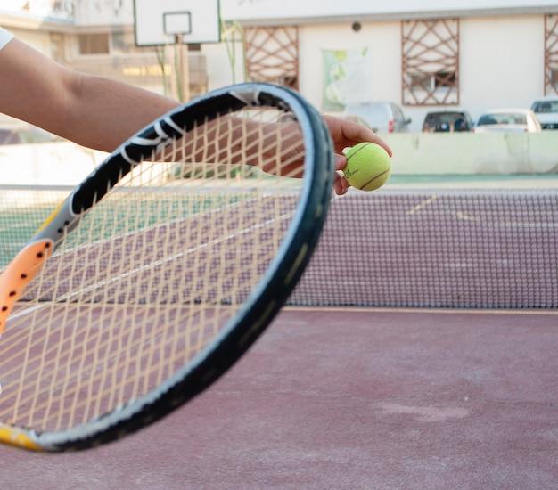 Uma raquete de tênis e uma bola de tênis no fundo de uma quadra de tênis.