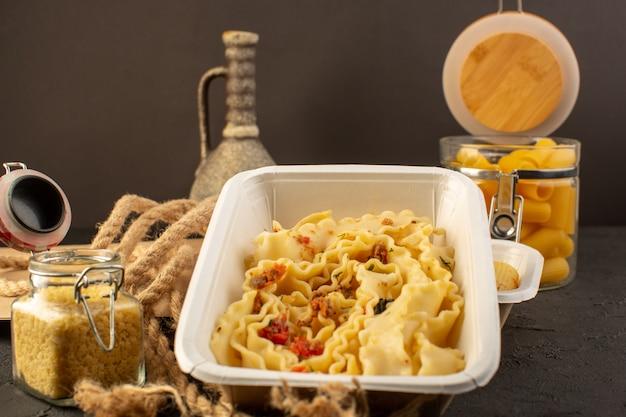Uma refeição de massa com ervas verdes secas dentro de uma tigela branca e pacote junto com massa italiana crua no escuro