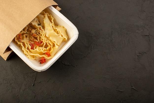 Uma refeição de massa com vista de cima com tomate e carne dentro de uma tigela branca e pacote no escuro