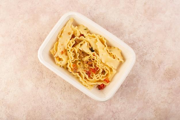 Uma refeição de massa com vista de cima com tomate e carne dentro de uma tigela branca em rosa