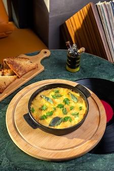 Uma refeição de ovo de vista de cima dentro de uma panela com pão na mesa.