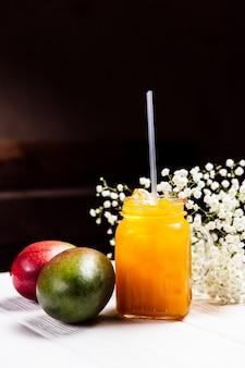 Uma refrescante limonada de manga em uma jarra, na mesa de madeira branca