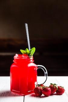 Uma refrescante limonada de morango e hortelã em uma jarra, na mesa de madeira branca
