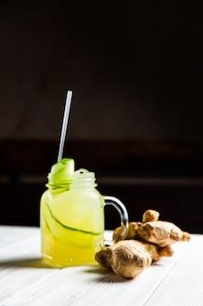 Uma refrescante limonada de verão com pepino e gengibre em uma jarra, na mesa de madeira branca
