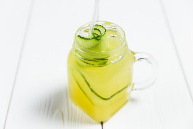Uma refrescante limonada de verão com pepino em uma jarra, na mesa de madeira branca