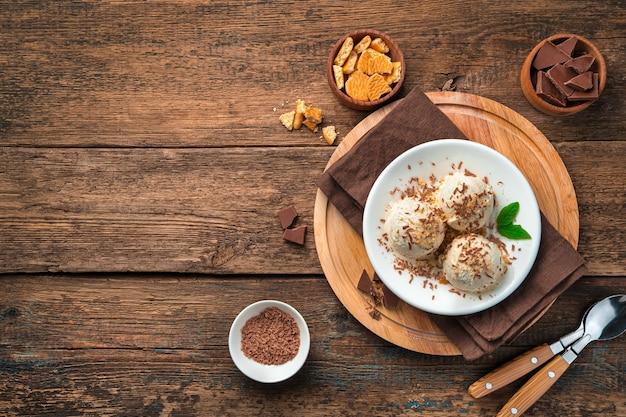Uma refrescante sobremesa de bolas de sorvete polvilhada com gotas de chocolate e migalhas de biscoito em uma mesa de madeira marrom