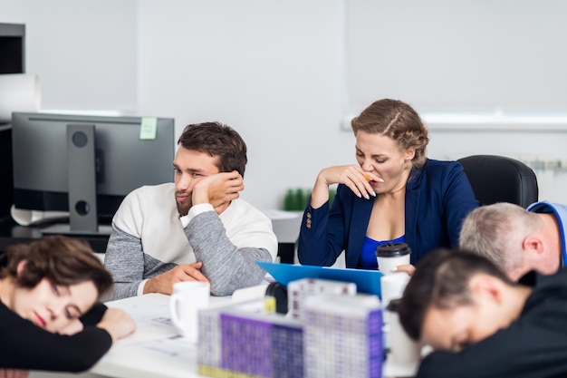 Uma reunião de negócios cansativa, trabalhadores de escritório não produtivos, bocejantes e entediados em uma reunião