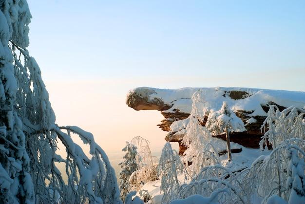 Uma rocha de arenito cercada por árvores cobertas de neve no topo de uma montanha em um dia frio e ensolarado de inverno