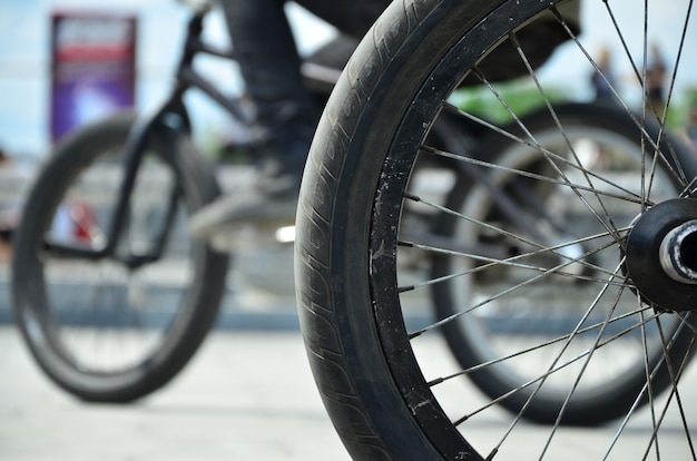 Uma roda da bicicleta de bmx contra uma rua borrada com cavaleiros de ciclagem. conceito de esportes radicais