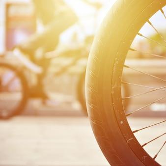Uma roda de bicicleta de bmx contra o pano de fundo de uma rua turva com ciclistas. conceito de esportes radicais