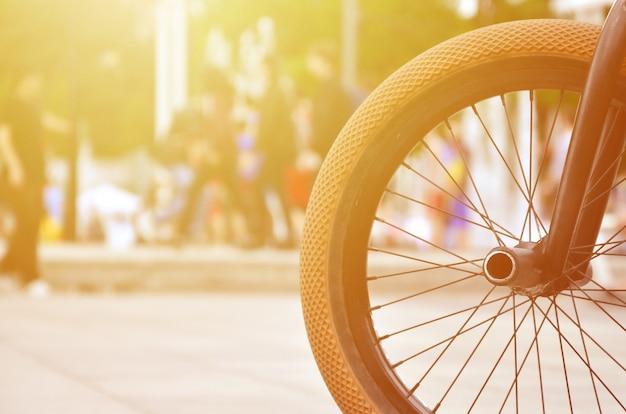 Uma roda de bicicleta de bmx contra o pano de fundo de uma rua turva com ciclistas.