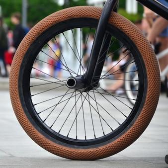 Uma roda de bicicleta de bmx contra o pano de fundo de uma rua turva com ciclistas