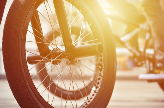 Uma roda de bicicleta de bmx contra o pano de fundo de uma rua turva